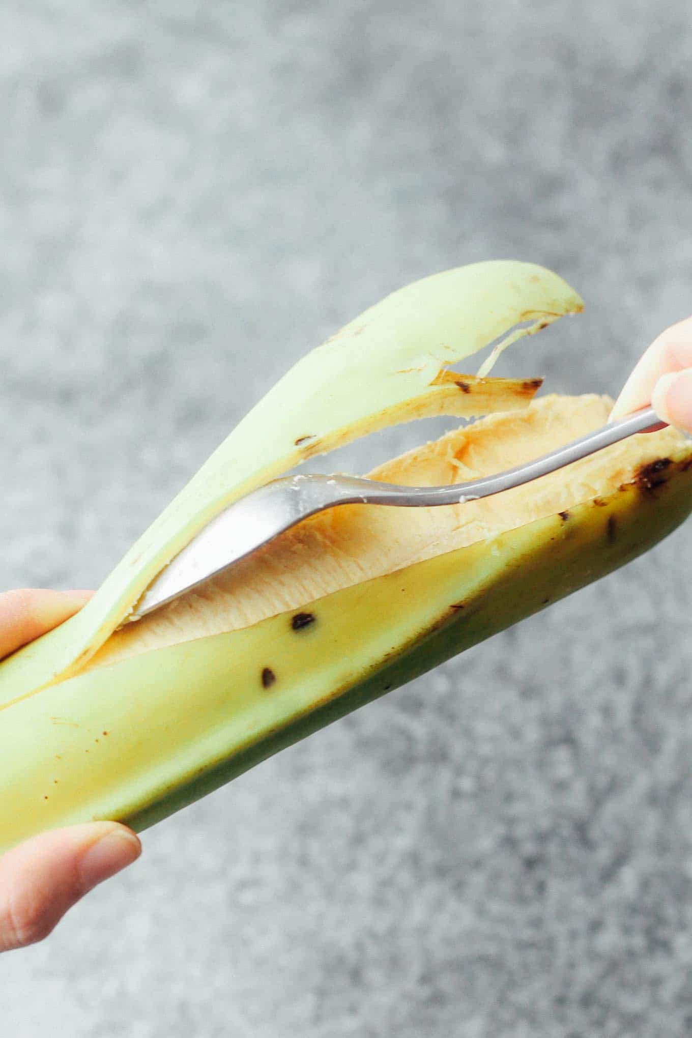 A plantain being peeled with a spoon