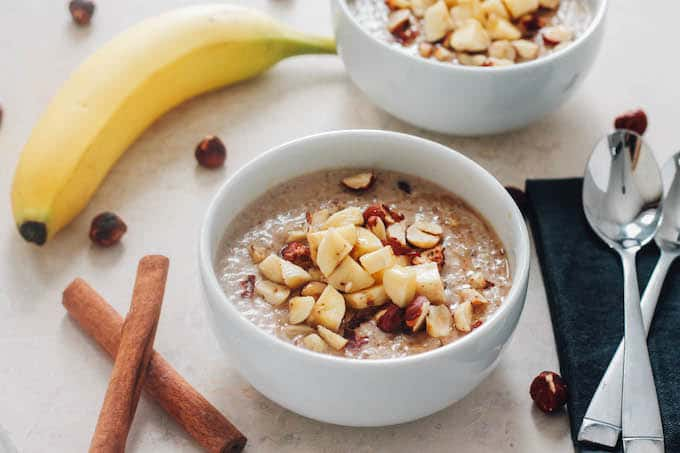 Banana Hazelnut Breakfast Quinoa | Destination Delish - Cozy up to a bowl of this wholesome breakfast quinoa with chopped hazelnuts and bananas and sweetened with maple syrup.