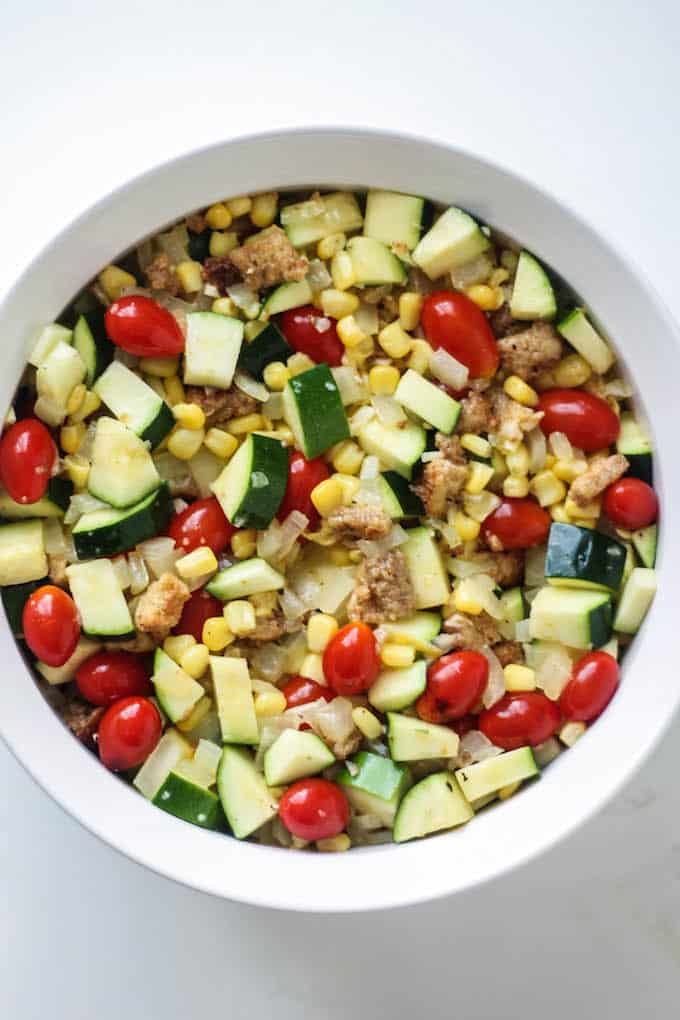 Zucchini, Corn, and Tomato Casserole | Destination Delish - An Italian inspired dish celebrating summer produce topped off with crispy bread cubes and melted mozzarella