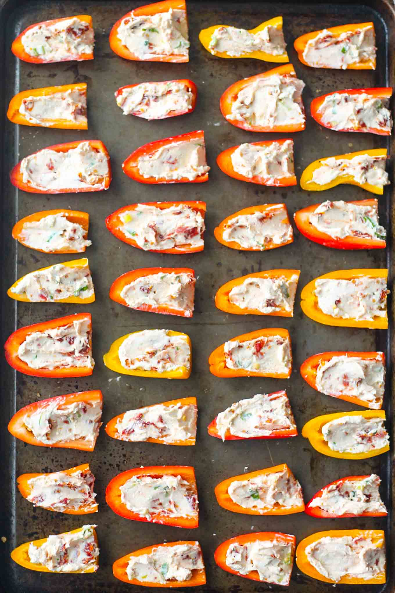 Pre-baked stuffed peppers on a sheet pan.