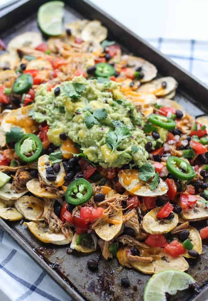 Pulled Pork Plantain Nachos | Destination Delish - healthier nachos using baked plantain wedges topped with tender pulled pork, black beans, and all your fave toppings