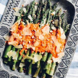 Grilled Asparagus with Romesco | Destination Delish – Tender grilled asparagus with tangy red pepper sauce make up this easy and healthy side dish. Pair it with your favorite grilled protein for the ultimate summer meal!