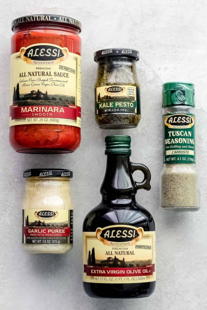 Alessi products, including marinara sauce, kale pesto, Tuscan seasoning, garlic puree, and olive oil, grouped together.