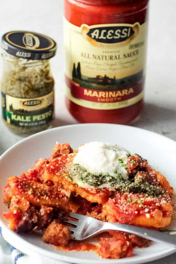A bite being taken out of the plated casserole with jars of pesto and marinara sauce in the background