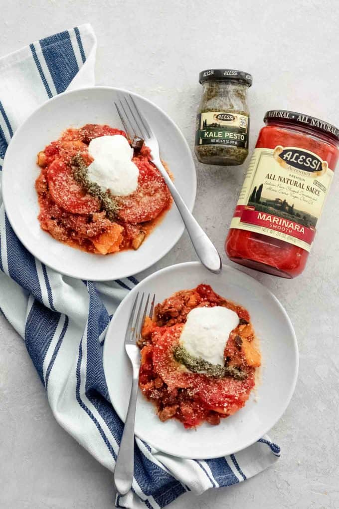 Plated casserole on two plates with jars of pesto and marinara sauce on the side.
