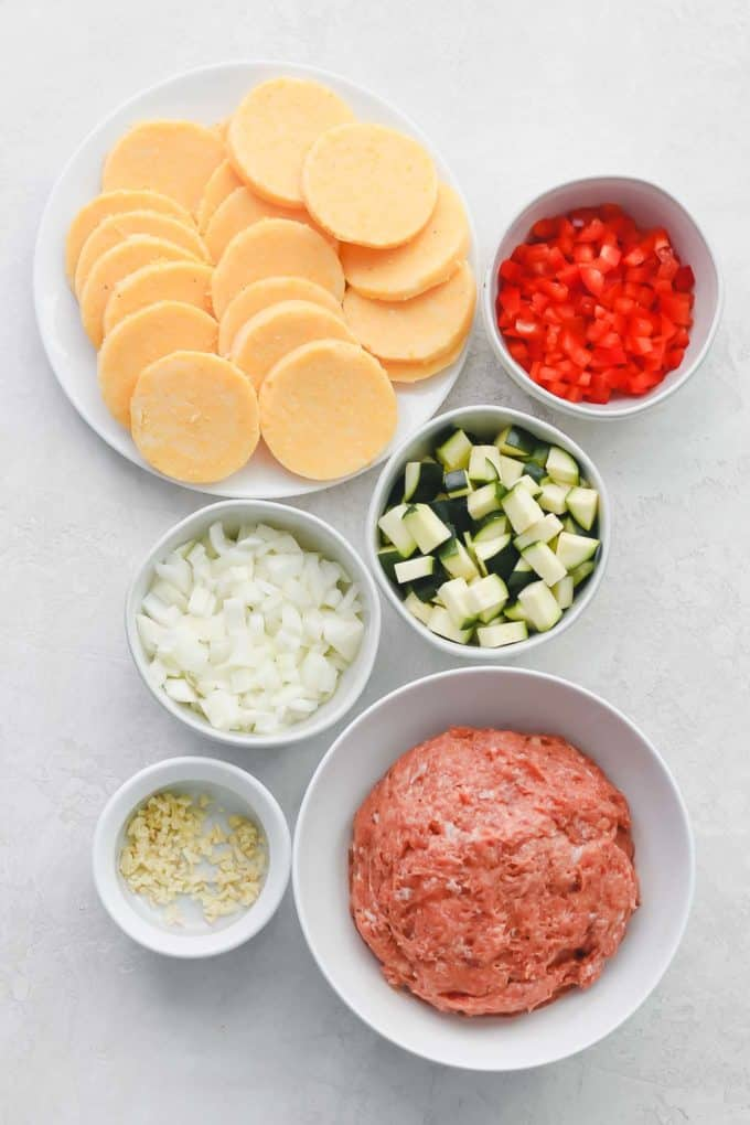 Portioned out ingredient including polenta, red pepper, zucchini, onion, garlic, and turkey sausage