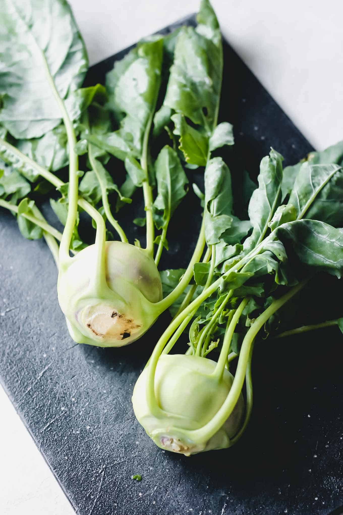 Kohlrabi with stems and leaves on a cutting board