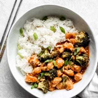 Orange chicken and broccoli in a bowl with a side of rice