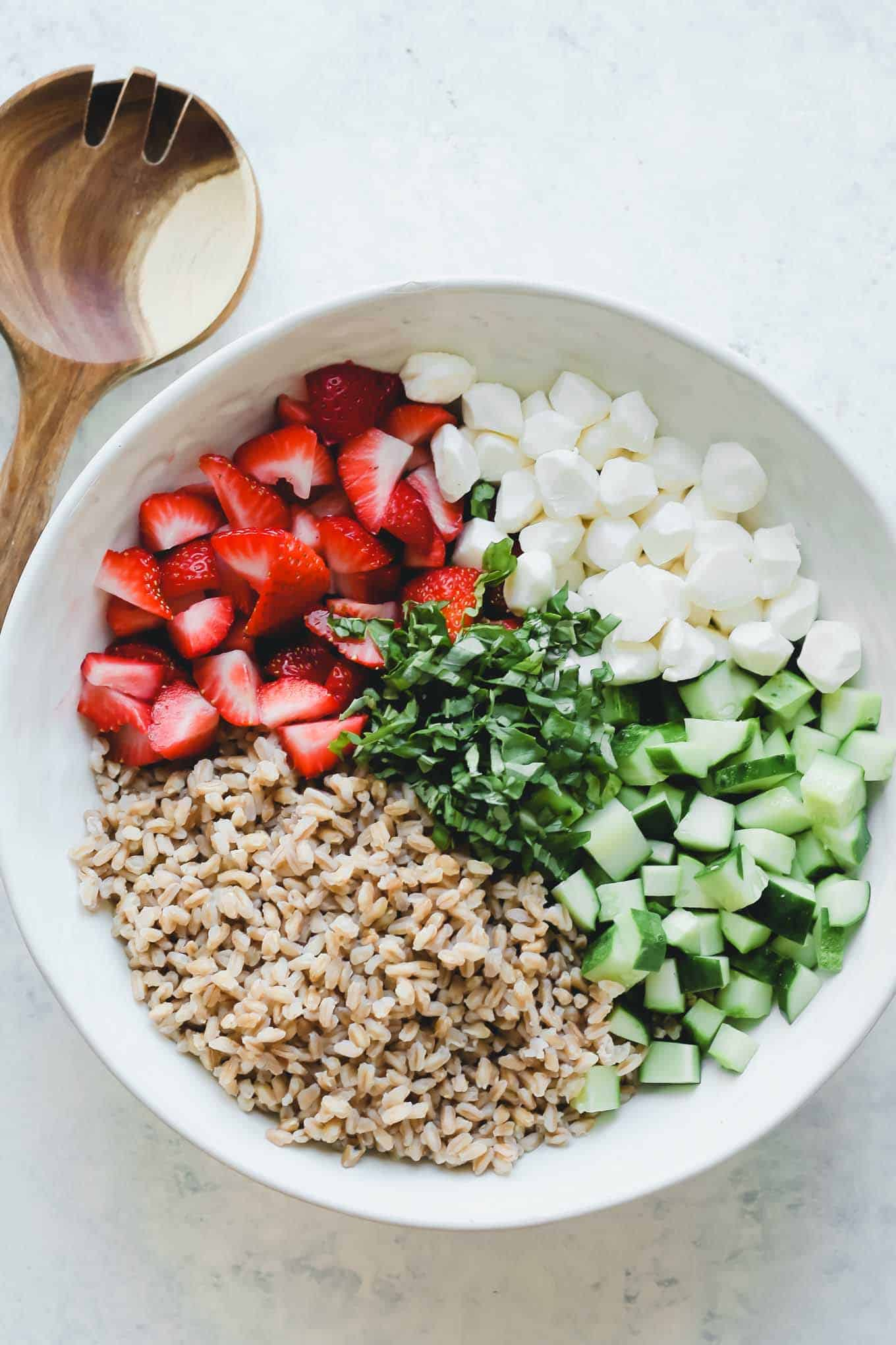 Cucumbers, strawberries, fresh mozzarella pearls, farro, and basil separated into piles in a salad bowl