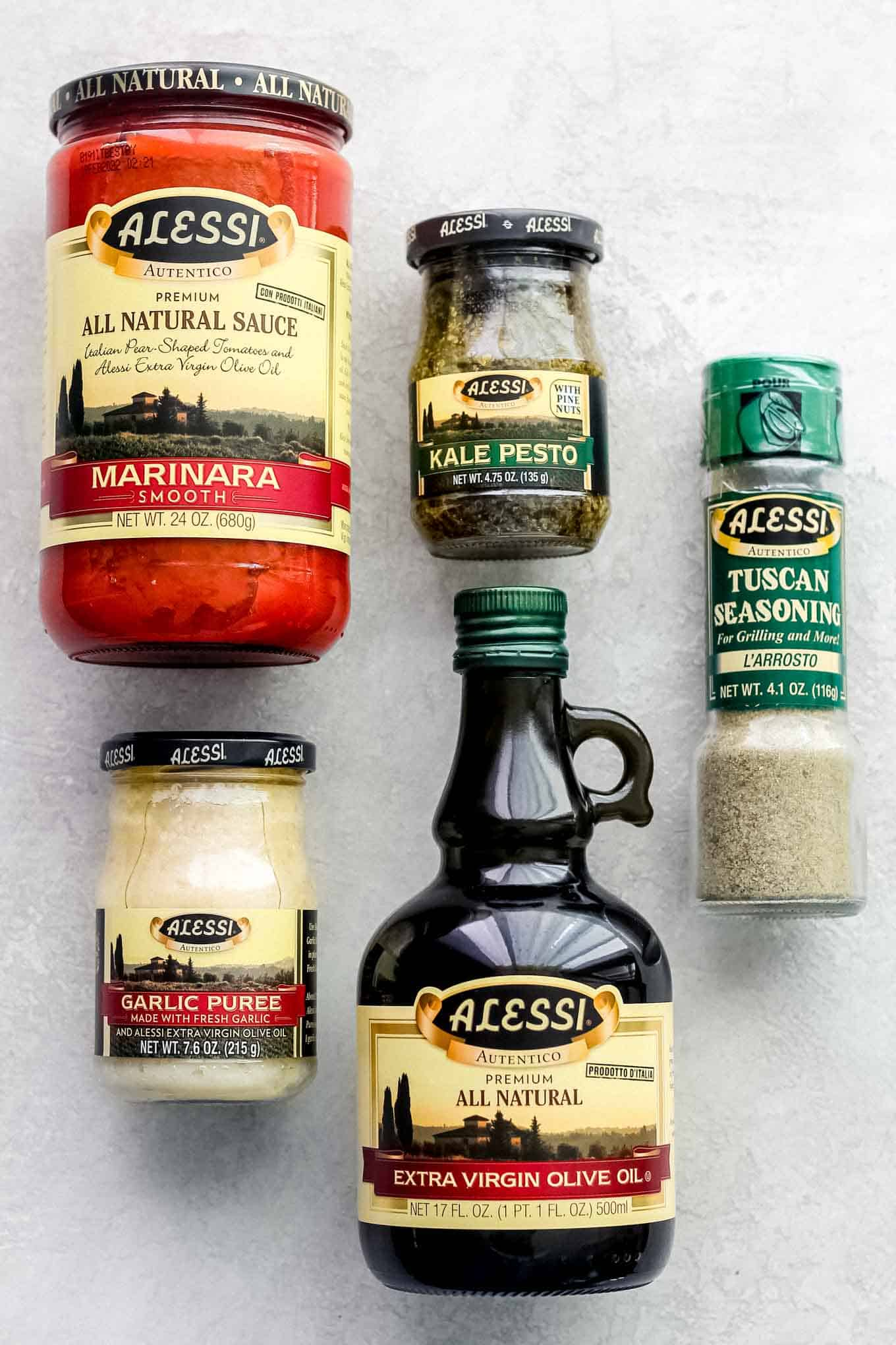 A collection of Alessi products including marinara sauce, kale pesto, Italian seasoning, olive oil, and garlic puree.