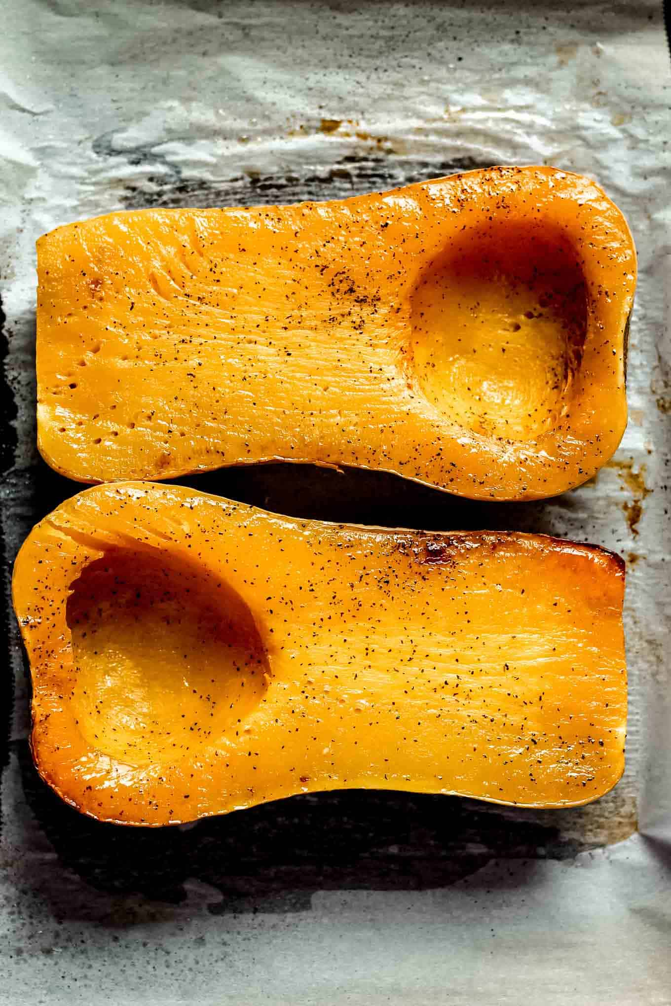 Roasted butternut squash halves on a sheet pan after