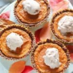 Four mini pies on a cake stand with fall leaves surrounding them