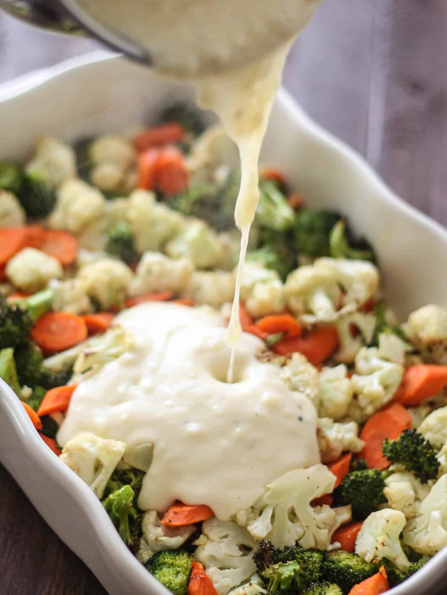 Pouring the cheese sauce over the roasted vegetables in the dish