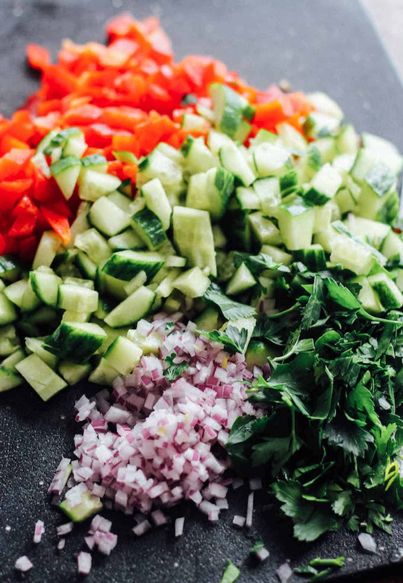 Chopped red bell pepper, cucumber, red onion, and parsley on a cutting board.