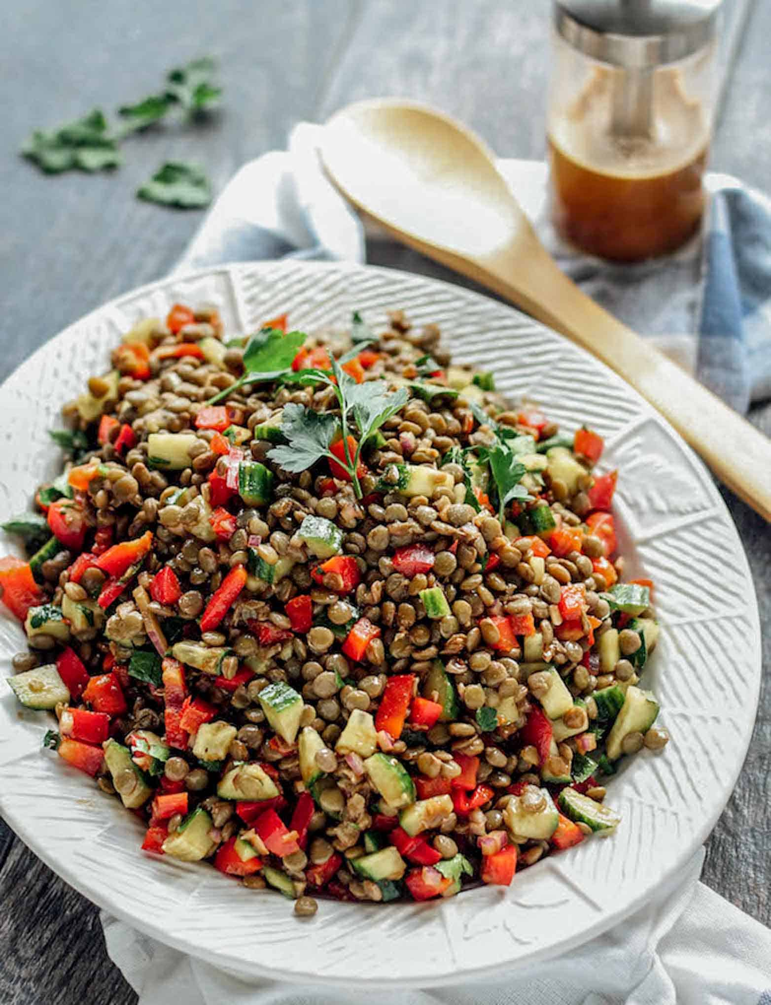 The Balsamic Lentil Salad shown on a platter with a serving utensil and a jar of dressing on the side