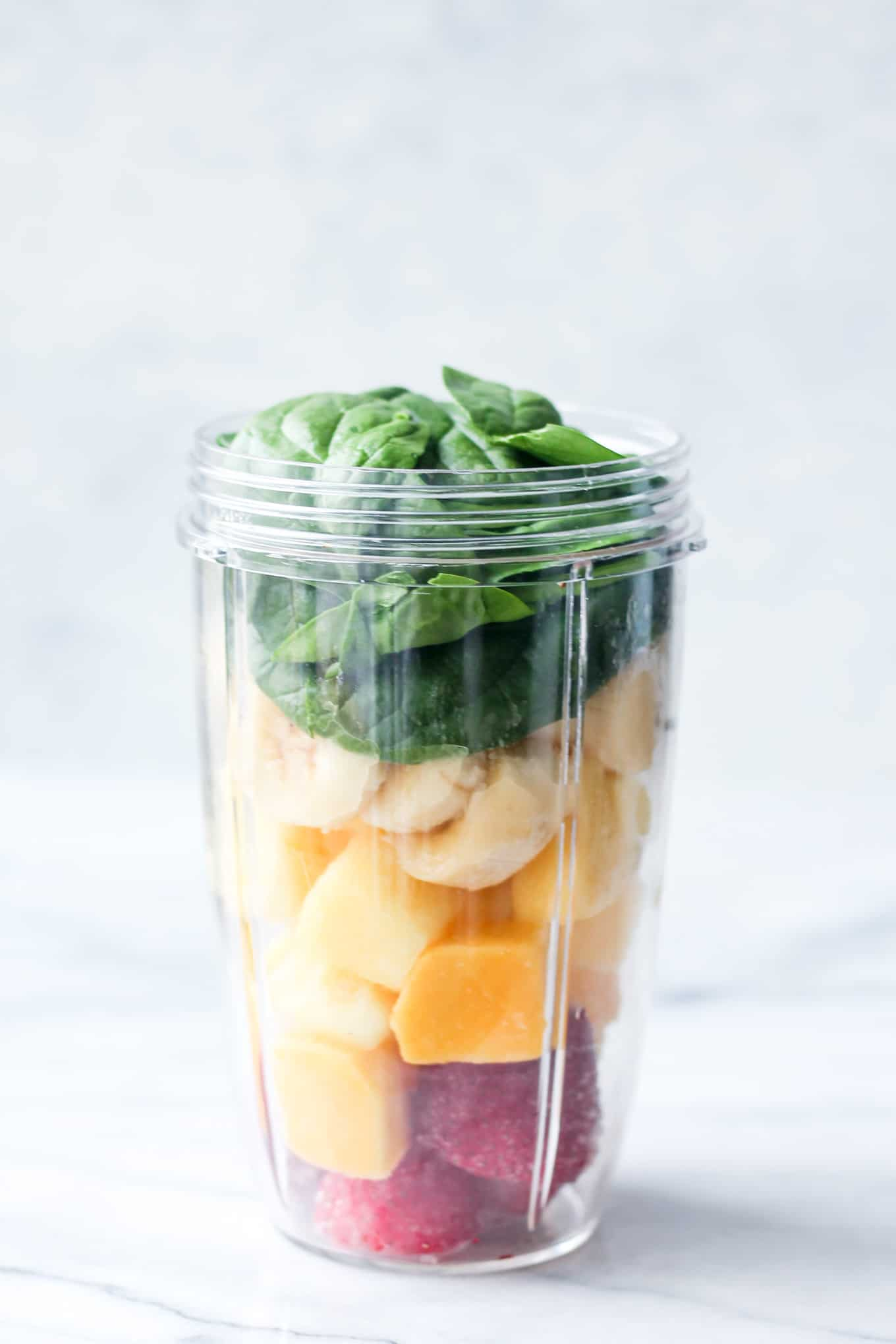 Strawberries,  mango, banana, pineapple chunks, and spinach packed in a blender before blending.