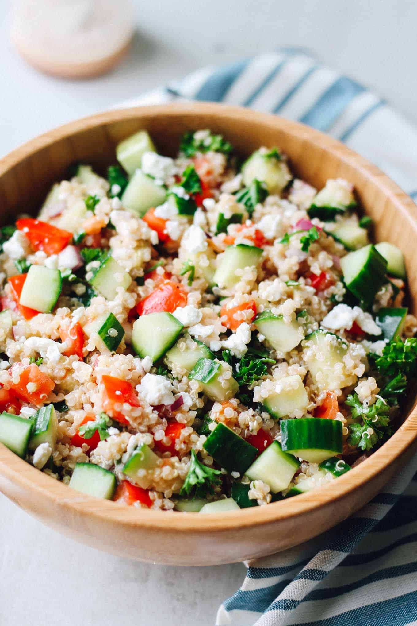 The Greek Quinoa Salad in a wooden bowl with a close up on the ingredients