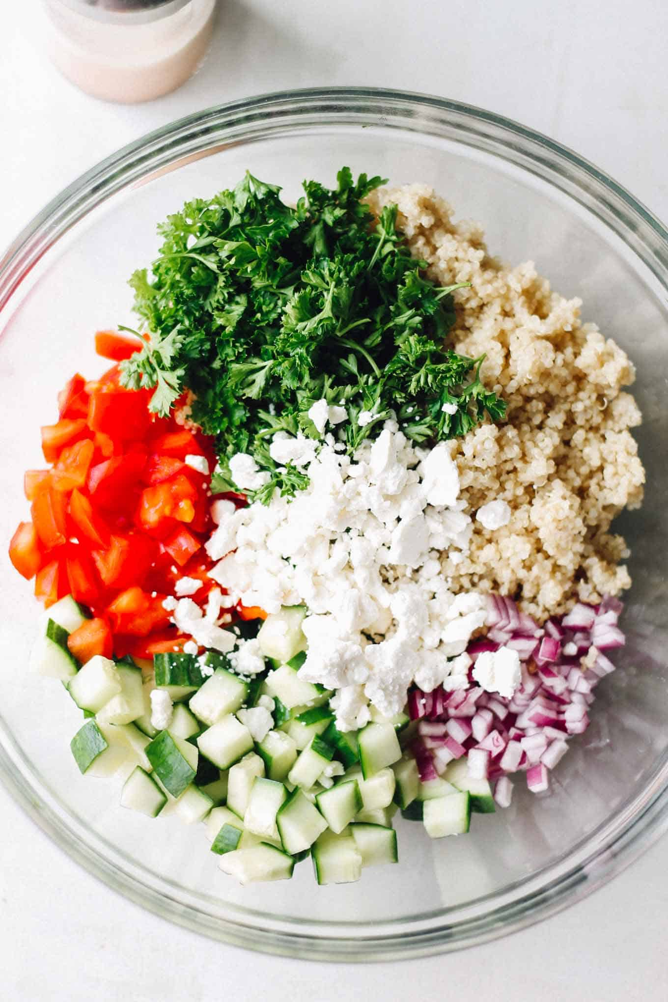 Quinoa, red onion, cucumber, tomatoes, parsley, and feta in a glass bowl before tossing the salad.