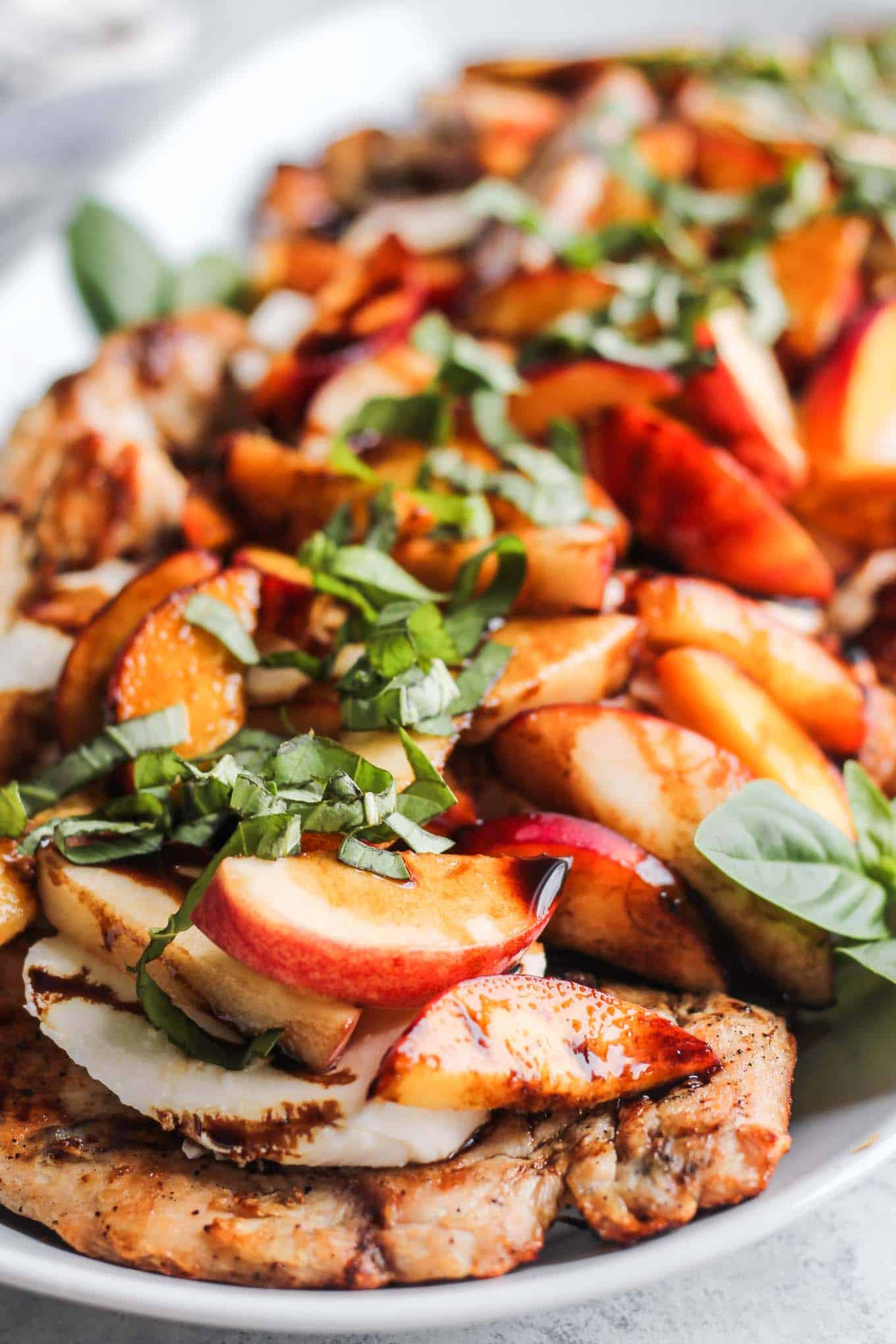 A close up view of the plated Peach Caprese Grilled Chicken