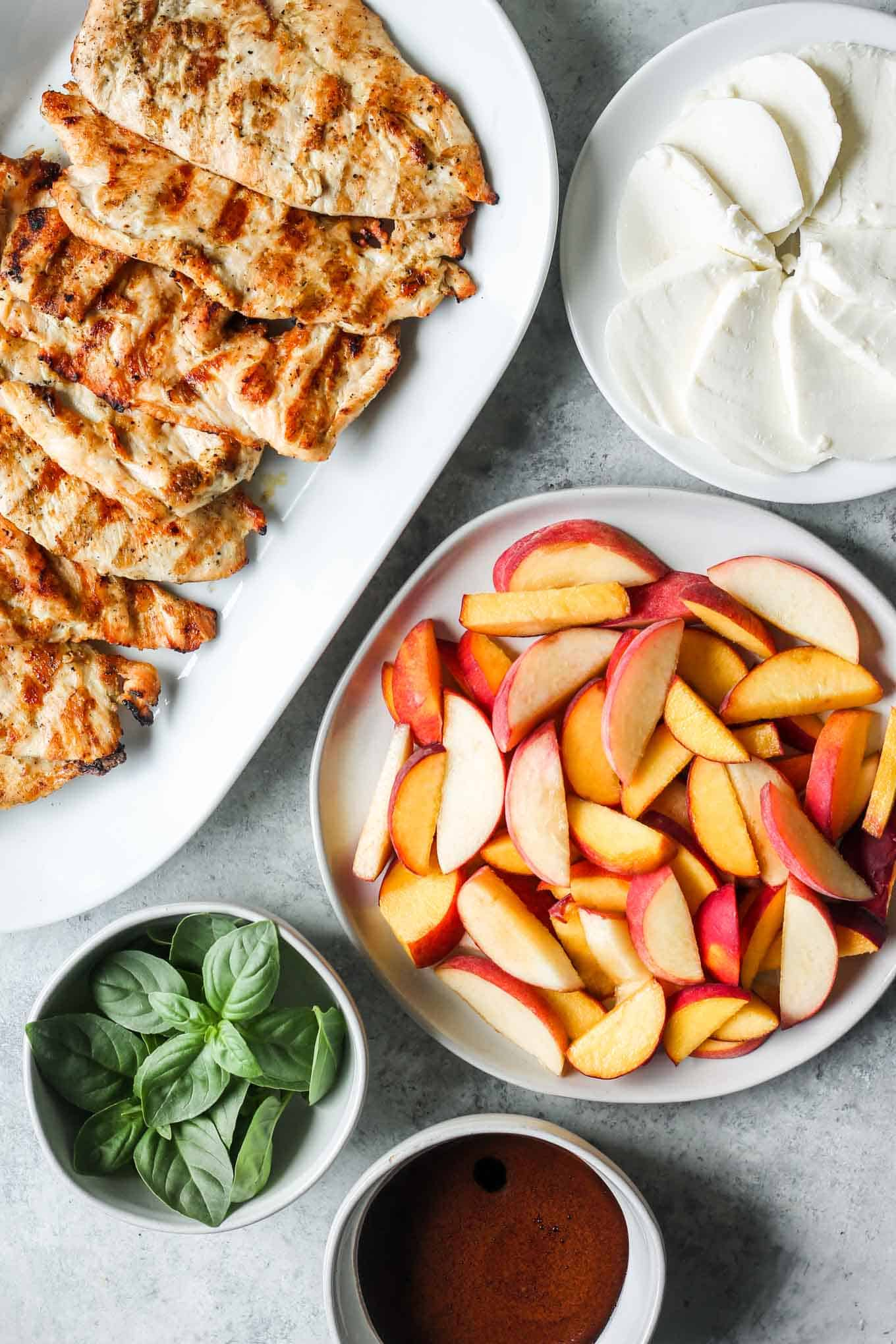 The peach slices, mozzarella slices, grilled chicken, basil, and balsamic glaze portioned out and ready to be assembled.