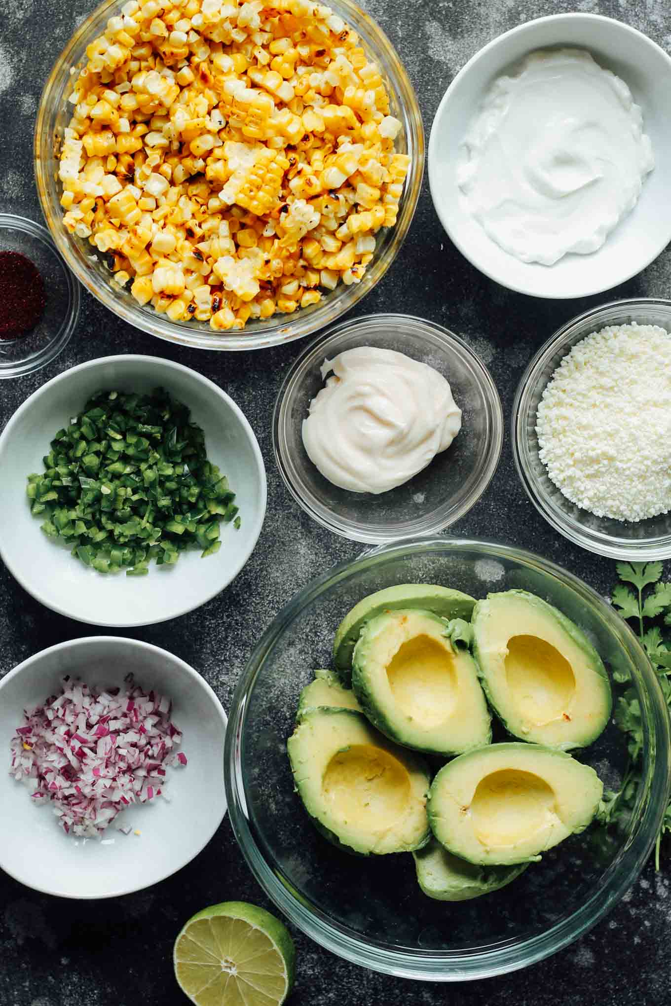 All of the Elote Guacamole ingredients portions out in bowls.